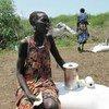 امرأة في دورين بجنوب السودان، تجلس بجانب المساعدة الغذائية التي تلقتها للتو لعائلتها من برنامج الأغذية العالمي.