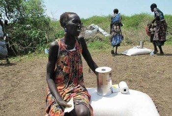 Mwanamke akiwa Dorein, Sudan Kusini, akiwa ameketi kandoni mwa mgao wa chakula uliotolewa na WFP kwa ajili ya familia yake.