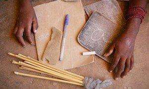 Une fille présente ses fournitures scolaires dans une école primaire administrée par l'UNICEF dans le village de Guivagou, au Mali.