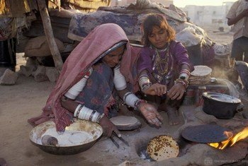 Migrant workers in India cook a meal.