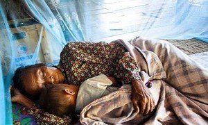 With support from a Global Fund grant, a woman and a child sleep under an insecticide-treated net in Atsapanethong District, Laos.