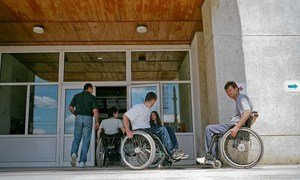 Men and women at the entrance of a school in Romania that teaches people with disabilities.