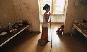 Una mujer que sufre de VIH/SIDA en Camboya utiliza un bastón para regresar a su cama en el hospital.