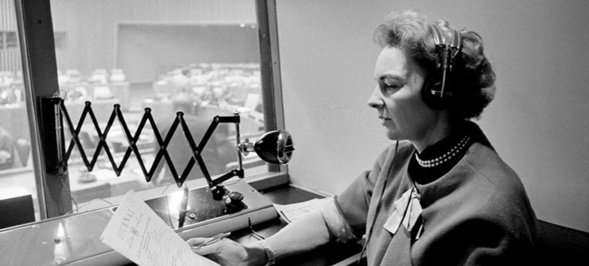 Highly skilled interpreters perform a vital service at UN meetings, where delegates come together to present their views in one of the six official languages or in their own tongue. A UN Interpreter, at work in a booth over looking a meeting room. (1965)