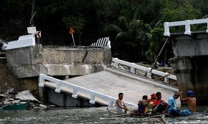 Survivors of a 7.2 magnitude killer quake that struck the central Philippines use a small canoe to cross a river after the main bridge connecting the hardest hit town of Loon in Bohol.