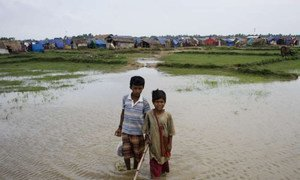 Two displaced boys in Rakhine state, Myanmar, play in a river. Daily life is still a struggle for communities like theirs and some people risk their lives at sea in their search for safety and stability.