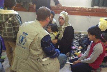 Des employés du Programme alimentaire mondial (PAM) distribuent des rations alimentaires à des familles déplacées en provenance de Yarmouk, en Syrie.