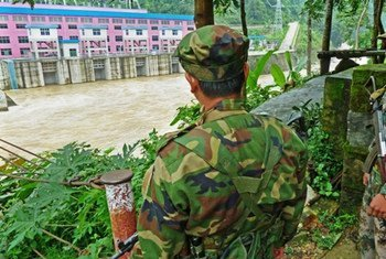 Two Kachin soldiers stand guard opposite a Chinese dam in northern Kachin state, where more than 85,000 people have been displaced by conflict. Photo: IRIN/Steve Sandford