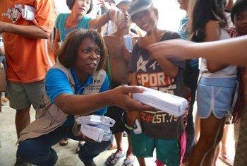 La Directrice exécutive du Programme alimentaire mondial (PAM) distribue des biscuits à des enfants philippins à Tacloban.