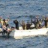 Des pirates présumés attendent les mains en l'air que des membres d'une opération de lutte contre la piraterie montent à bord de leur embarcation (archives). Photo US Navy/Jason R Zalasky