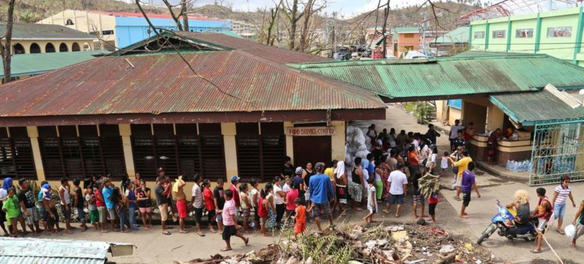 Families in the Philippines queue up to receive food rations, including WFP rice, from the Department of Social Welfare and Development.