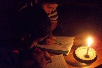Children read by candle light due to limited hours of electricity in the Gaza Strip.