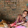 HIV positive Monica and her granddaughter sit at home on a bed in their village of Makuzeze, Zimbabwe.