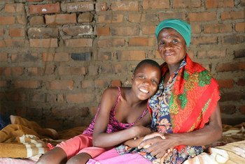 津巴布韦马库兹泽村的艾滋病病毒呈阳性的莫妮卡和她的孙女坐在家中的床上。