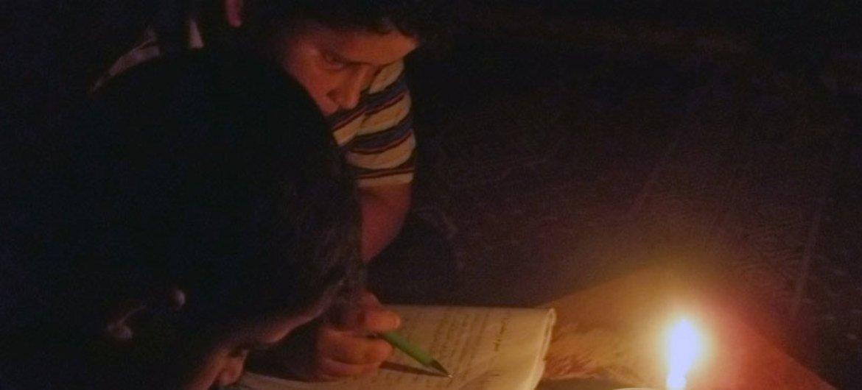 طفلان يذاكران على أضواء الشموع في غزة