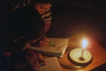 Two children read by candle light in Gaza.