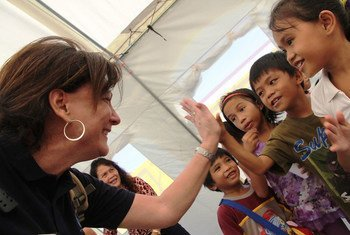 Resident and Humanitarian Coordinator Luiza Carvalho cheering children at temporary learning centre in Palo central school, the Philippines, during a donors mission to the region devastated by Typhoon Haiyan.