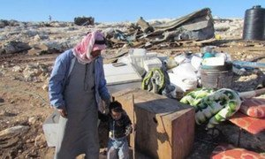 Father and son standing with their belongings following the latest demolitions in the West Bank, which displaced 68 people.