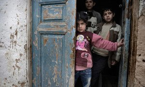 Syrian children shelter in the doorway of a house, amid gunfire and shelling, in a city affected by the conflict.