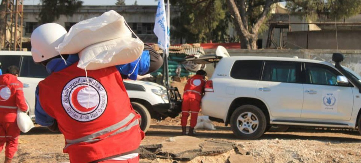 Syrian Arab Red Crescent (SARC) staffers carrying WFP aid for people stranded in besieged Old Homs City during a humanitarian pause in the fighting.