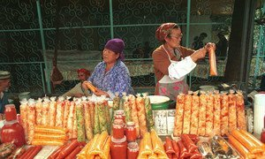 Women prepare, package and sell food at a market.