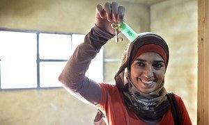 Syrian refugee Fatimah smiles while showing the key to her room at a new collective shelter in Kherbet Dawood in northern Lebanon. After fleeing the Syrian conflict with her family, she is excited to now have a room for just herself and her husband.