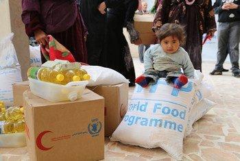 一个正在等待联合国分发救援食品的小女孩儿。联合国世界粮食署图片/Dina El-Kassaby