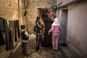 A Syrian mother and her children arrive at the dilapidated basement building where they are staying in Amman, the capital of Jordan.