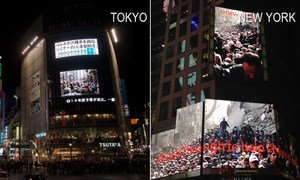 """The iconic image of a huge crowd waiting for UNRWA food parcels in the Palestinian refugee camp of Yarmouk, Damascus has gone up simultaneously on the """"Jumbotron"""" billboard in New York's Times Squareand in Tokyo's Shubyia district on the same day"""