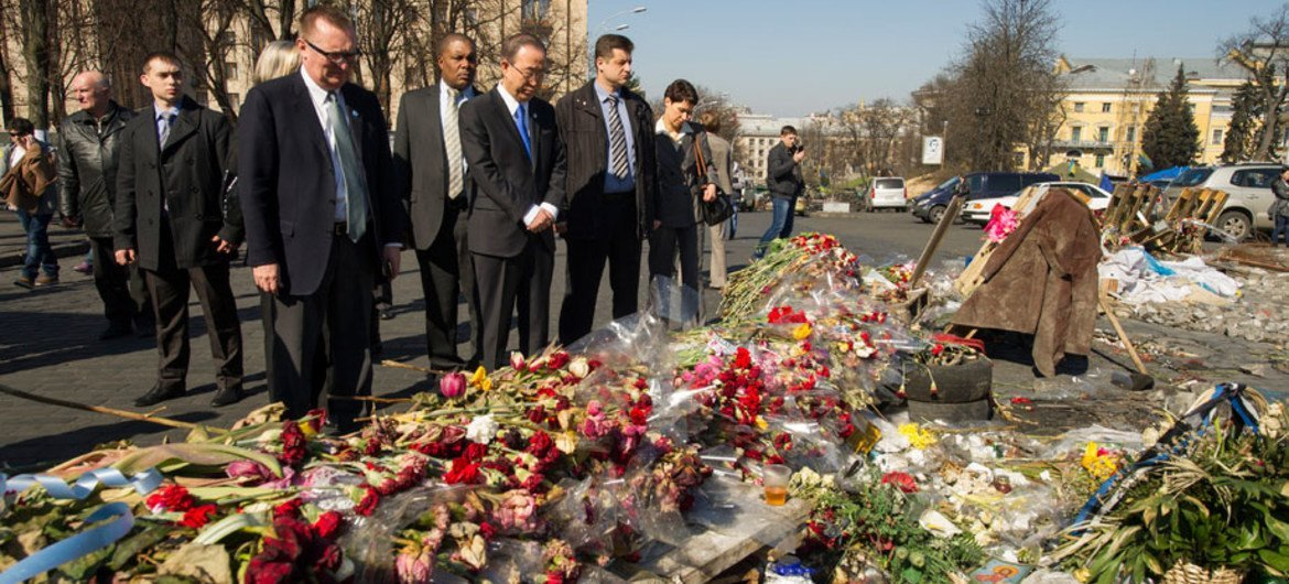 Secretary-General Ban Ki-moon (centre) pays his respects at a makeshift memorial for the victims of the recent violence in Kyiv.