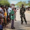 Residents of the village of Modmoday, 40 kilometres east of the town of Baidoa, Somalia, look on as a soldier of the Somali National Army (SNA) keeps guard.