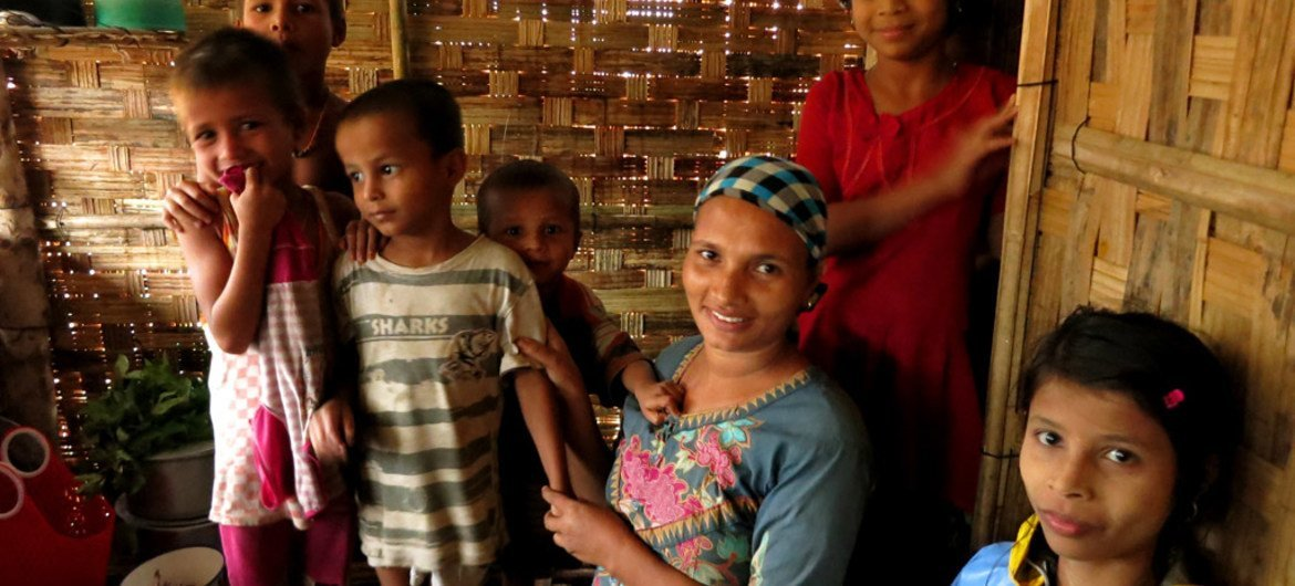 A mother and her children stand in their small hut in a camp for displaced people in Rakhine State.