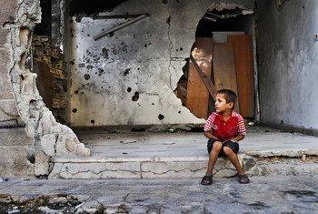 Un garçon assis devant un bâtiment détruit à Homs, en Syrie. Photo PAM/Abeer Etefa (archive septembre 2012)