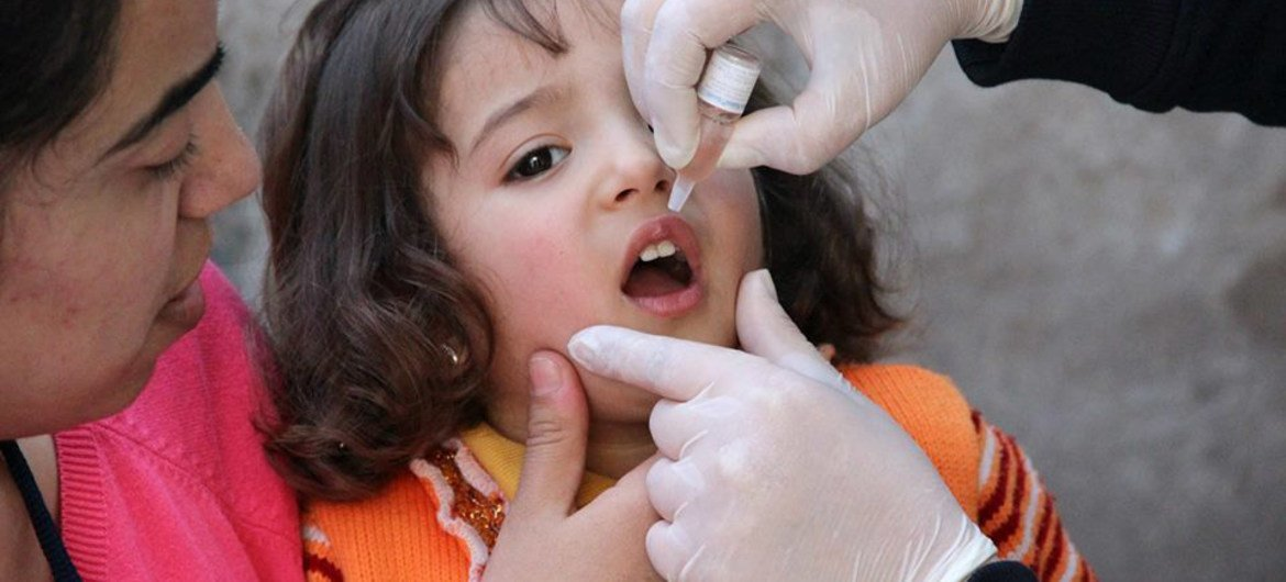 A child being administrated a dose of polio vaccination. Immunization programmes are a key element to strong health-care systems.