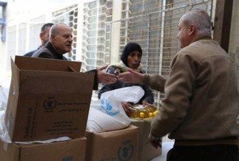 برنامج الأغذية العالمي يقوم بتوزيع حصص غذائية على السكان . صورة لبرنامج الأغذية العالمي / دينا