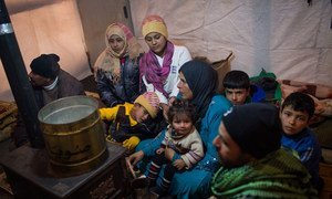 Members of a Syrian refugee family huddle around a stove inside their shelter in Lebanon's Bekaa Valley.