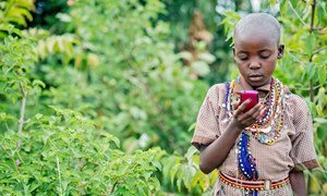 In countries where physical books are hard to come by and illiteracy rates are high, mobile technology is being used to facilitate reading and improve literacy, says UNESCO.  Shown, in Kenya, a Masai girl reads on an Android phone.