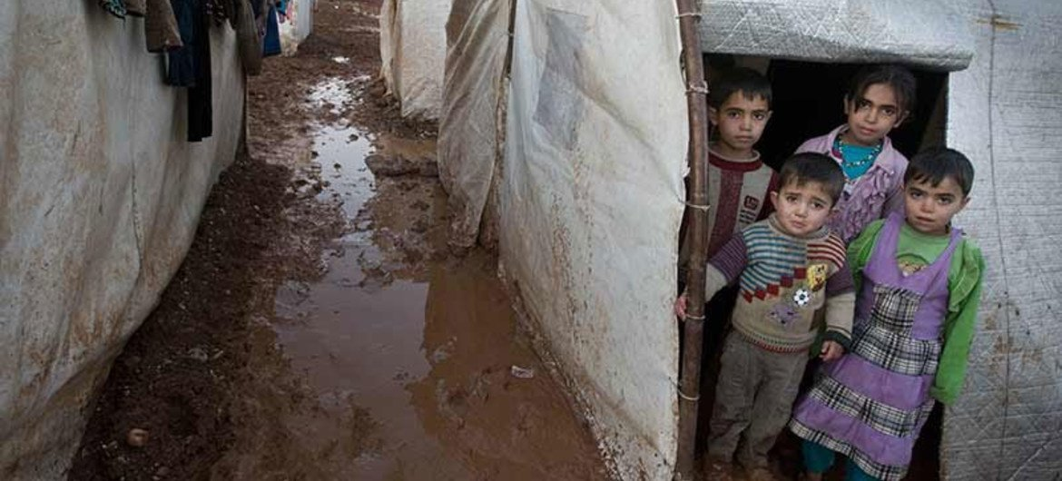 Syrian children stand in the entryway of their tent shelter in the Bab Al Salame camp for internally displaced persons in Aleppo Governate.