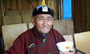 An elderly Mongolian herder drinks fermented mare's milk in Ulaanbaatar.