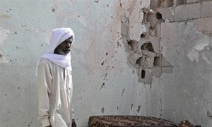 A resident of Tayuri stands against a bullet-riddled wall of his house, part of which was destroyed during clashes in Libya.