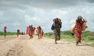 Des déplacés arrivant dans un camp près d'une base de la Mission de l'Union africaine en Somalie (AMISOM), près de Jowhar. Photo ONU/Tobin Jones