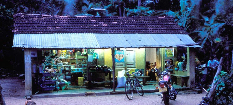 Village shop at dusk in Sri Lanka lit by solar panels.
