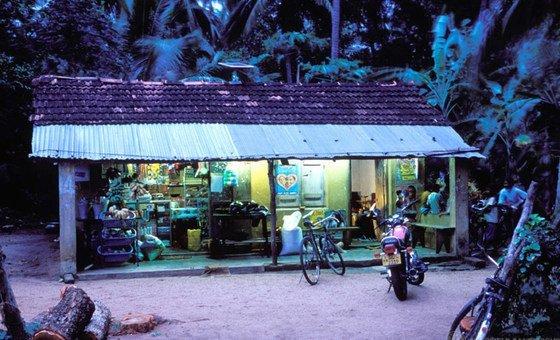 Un magasin dans un village au crépuscule au Sri Lanka éclairé par des panneaux solaires.