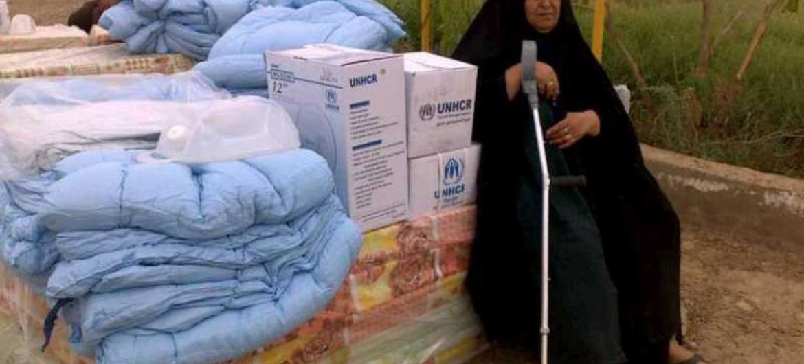 An Iraqi woman displaced by conflict in Anbar province, Iraq, rests on a pile of UNHCR mattresses.