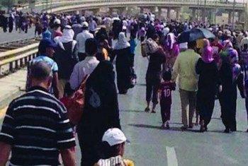 A Mossoul, en Iraq, des déplacés fuient la violence à pied. Photo OIM/MANUA
