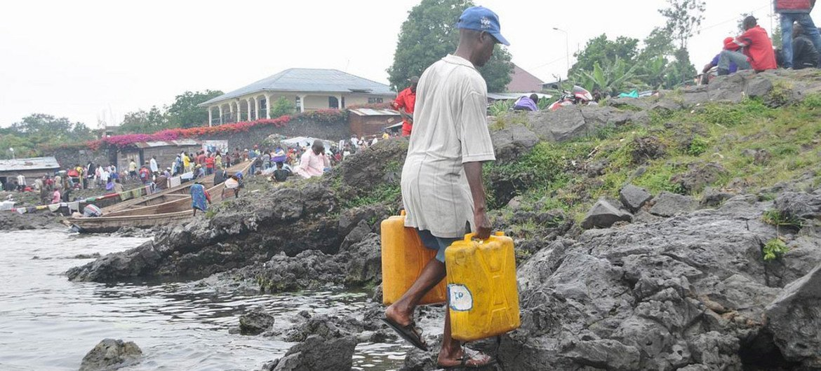 At the border with Rwanda, a resident of Goma, Democratic Republic of the Congo (DRC), collects water from Lake Kivu.