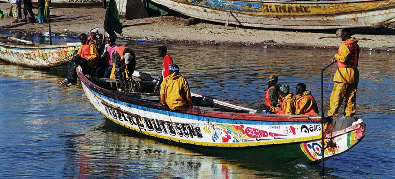 Municipal sanitation workers carry trash aboard boat in Guidimaka, Mauritania.