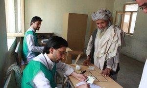 Des agents électoraux en Afghanistan aident un électeur lors du second tour du scrutin présidentiel le 14 juin 2014. Photo MANUA/Shamsudding Hamedi