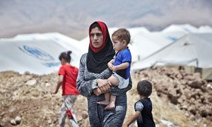 An Iraqi woman from Mosul carries her son at the Garmava transit camp, located near a checkpoint on the road between Mosul and Duhok in Iraqi Kurdistan. The camp will have the capacity to host some 3,000 people.