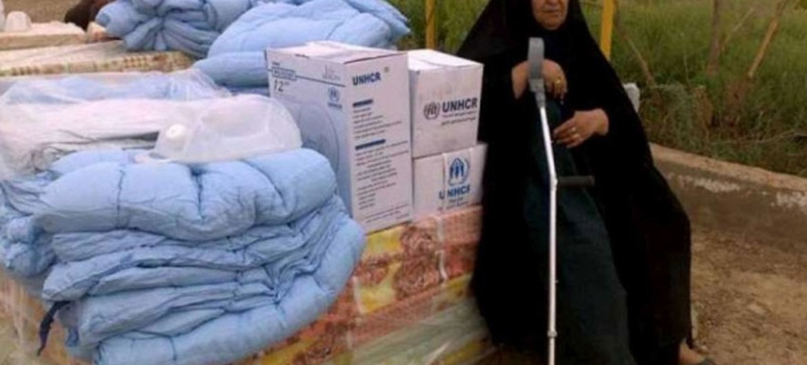 An Iraqi woman displaced by conflict in Anbar rests on a pile of UNHCR mattresses. The aid seen here was distributed shortly afterwards.